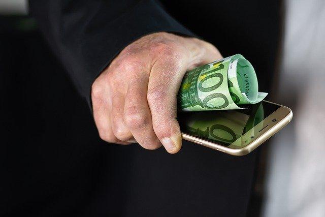 mobil a bankovka v ruce